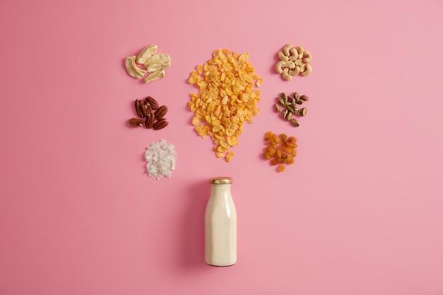 Zestaw płatków, pistacje, rodzynki, orzechy pekan, suszone jabłko, orzechy nerkowca, kokos wokół butelki mleka na białym tle na różowym tle. odżywcze śniadanie bogate w witaminy do spożycia, koncepcja odżywiania.