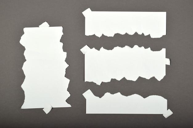 Zestaw podartych arkuszy papieru z naklejkami na szarym tle