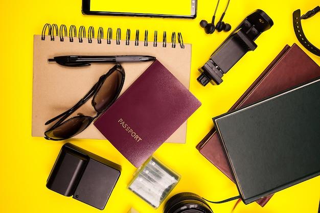 Zestaw podróżny hipsterskiej blogerki gotowy na letnie wakacje. żółte tło. płaski widok z góry
