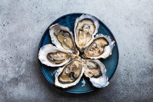 Zestaw pół tuzina świeżych ostryg otwartych w łupinach, podawanych na rustykalnym niebieskim talerzu na szarym tle kamienia, z bliska, widok z góry. koncepcja ostryg