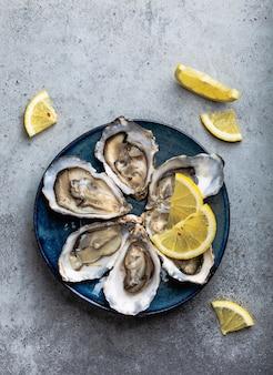 Zestaw pół tuzina świeżych, otwartych ostryg w skorupkach z klinami cytryny podanymi na rustykalnym niebieskim talerzu na szarym tle kamienia, zbliżenie, widok z góry