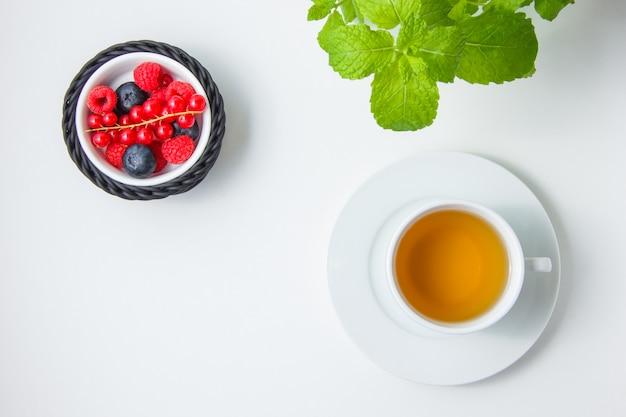 Zestaw porzeczki czerwonej, rumianku, liści mięty oraz jagód i malin w misce.