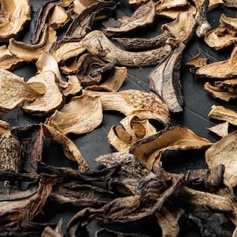 Zestaw posiekanych dzikich suszonych grzybów na czarnym tle