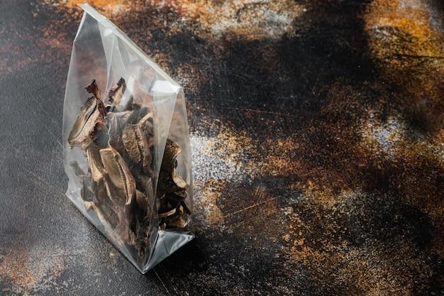 Zestaw posiekanych dzikich suszonych grzybów, na starym ciemnym rustykalnym tle, w plastikowym opakowaniu, z miejscem na tekst copyspace