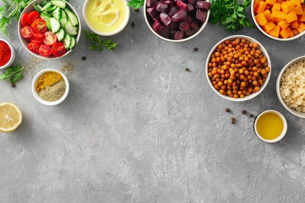 Zestaw potraw do gotowania zdrowych potraw wegetariańskich. przyprawiona ciecierzyca, pieczona dynia i buraki, komosa ryżowa i warzywa.