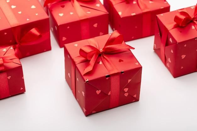 Zestaw prezentów w czerwonych pudełeczkach ozdobionych satynowymi wstążkami
