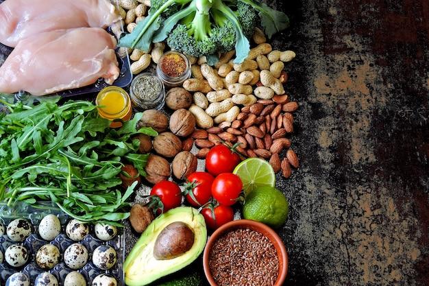 Zestaw produktów diety ketonowej o niskiej zawartości węglowodanów. zielone warzywa, orzechy, filet z kurczaka, nasiona lnu, jaja przepiórcze, pomidory koktajlowe.