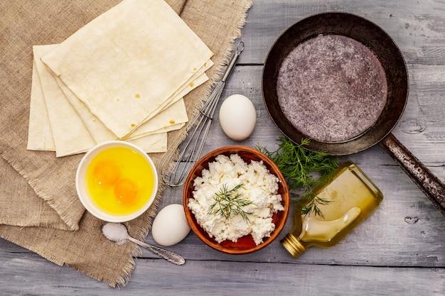 Zestaw produktów do gotowania gorącej przekąski. chleb pita, twarożek, jajka, warzywa, olej roślinny