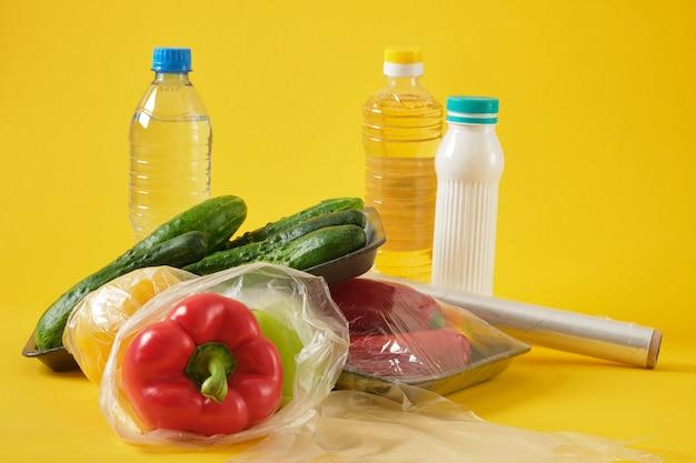 """Zestaw produktów w różnych plastikowych opakowaniach, plastikowa koncepcja zanieczyszczenia środowiska, powiedz """"nie"""" plastikowi, żółte tło kopii przestrzeni widok z góry"""