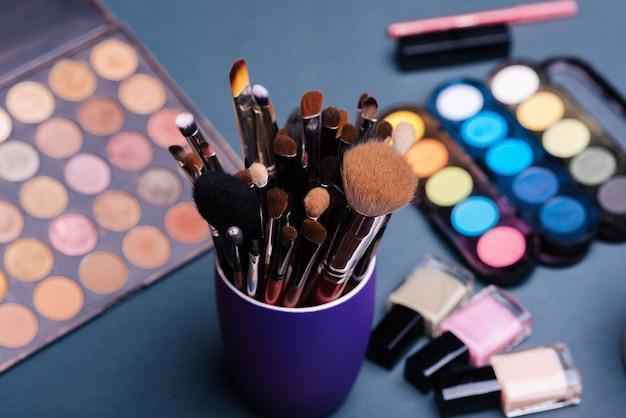Zestaw profesjonalnych pędzli do makijażu na tle palety z kolorowymi cieniami do powiek i kosmetykami