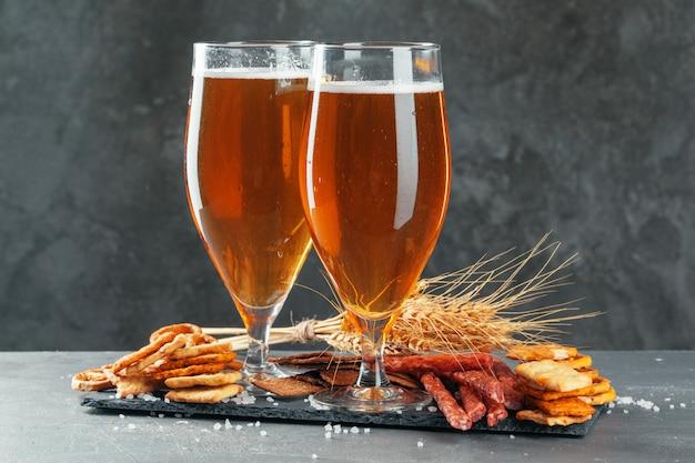 Zestaw przekąsek do piwa i piwa. stół z kuflem piwa, drewniana deska z kiełbaskami