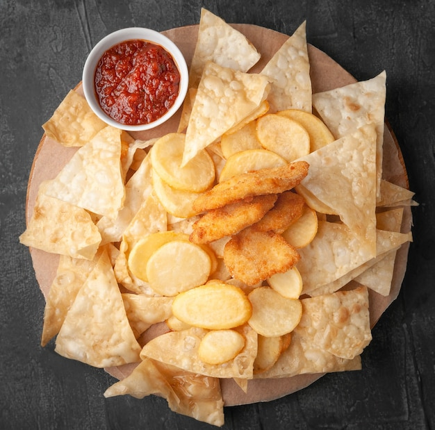 Zestaw przekąsek do piwa. składa się z chipsów nachos, frytek i nuggetsów. z sosem pomidorowym. podawany na okrągłej drewnianej desce. widok z góry. szare tło betonu.