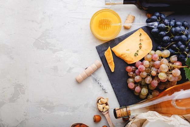 Zestaw przekąsek do wina na romantyczną kolację. różany szampan czerwone wino w butelkach z różnorodną przystawką na szarym, rustykalnym betonowym stole. deska serów winogrona miód orzechy. mieszkanie leżało z miejsca na kopię.