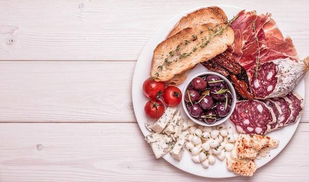 Zestaw przekąsek. rozmaitość ser i mięso, oliwki, pomidory na białym tle