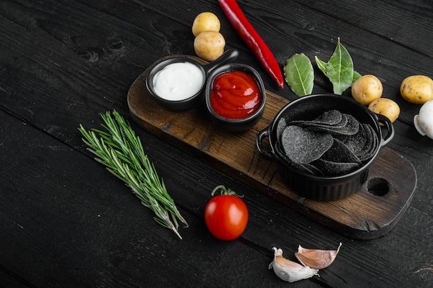Zestaw przekąsek z serem i szczypiorkiem, na czarnym drewnianym tle