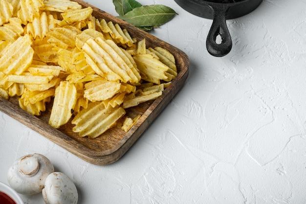 Zestaw przekąsek z solonymi chipsami ziemniaczanymi, z dipami pomidorowymi i śmietaną, na białej kamiennej powierzchni
