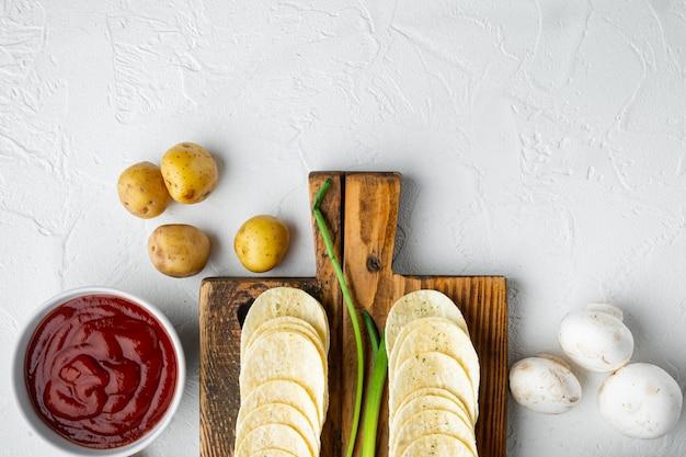 Zestaw przekąsek ze słonymi chipsami ziemniaczanymi, z maczanymi sosami dip pomidorowy z kwaśną śmietaną, na białej kamiennej powierzchni, widok z góry na płasko