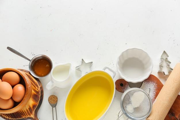 Zestaw przyborów kuchennych i składników do przygotowania piekarni na jasnym tle