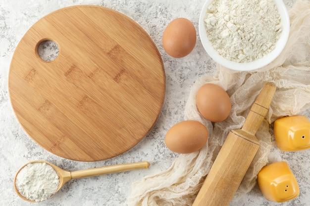 Zestaw przyborów kuchennych z produktami na białym tle.