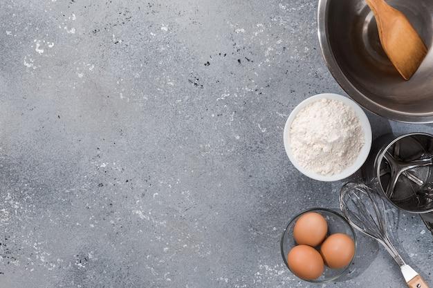 Zestaw przyborów kuchennych z produktami na szaro-niebieskim tle. kursy mistrzowskie gotowania. skopiuj miejsce.