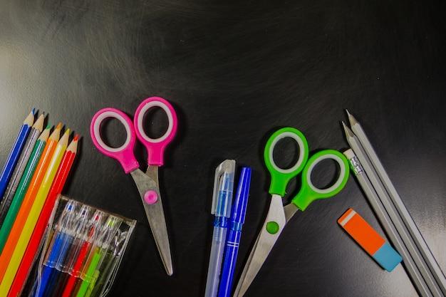 Zestaw przyborów piśmienniczych szkolnych. długopisy, ołówki, nożyczki i gumka na tablicy. powrót do koncepcji szkoły