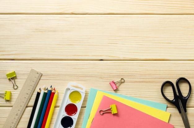 Zestaw przyborów szkolnych na jasnym tle drewniane. miejsce na tekst
