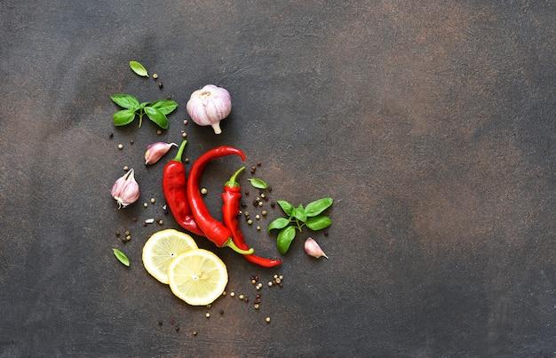 Zestaw przypraw, czosnku, świeżej bazylii i chili na betonowym tle. widok z góry.