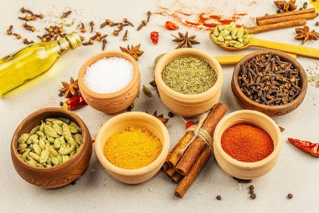 Zestaw przypraw do gotowania curry. aromatyczne przyprawy: kurkuma, papryka, kardamon, cynamon, anyż, chili, czarny pieprz, suszone zioła, sól. jasne kamienne tło betonowe, z bliska