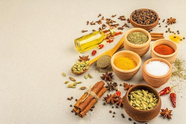 Zestaw przypraw do gotowania curry. aromatyczne przyprawy: kurkuma, papryka, kardamon, cynamon, anyż, chili, czarny pieprz, suszone zioła, sól. jasny kamień betonowy tło, kopia przestrzeń