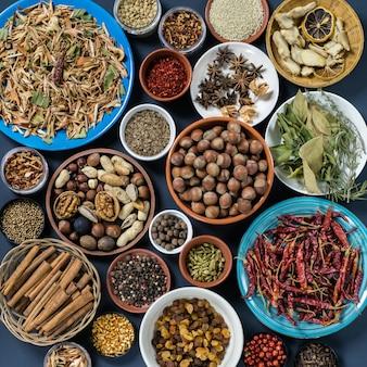 Zestaw przypraw i orzechów: trawa cytrynowa, cynamon, pieprz, anyż, rozmaryn, liść laurowy, imbir, orzechy laskowe, orzech, migdał, kolendra, badyan.