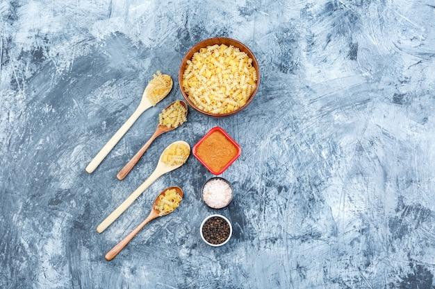 Zestaw przypraw i różne makarony w drewniane łyżki i miska na tle nieczysty tynk. widok z góry.