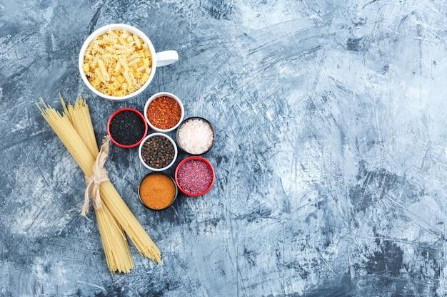 Zestaw przypraw i różne makarony w misce na szarym tle tynku. widok z góry.
