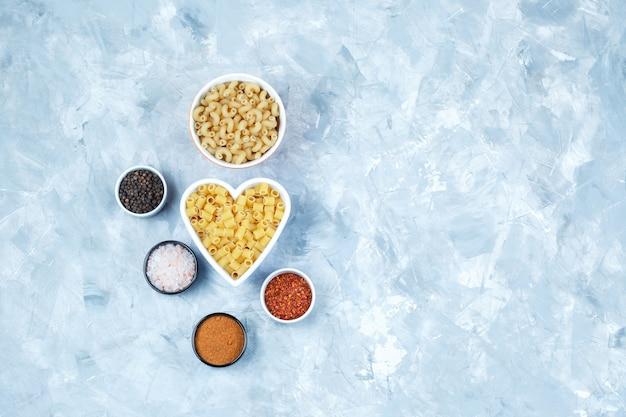 Zestaw przypraw i różne makarony w miski na szarym tle nieczysty. widok z góry.