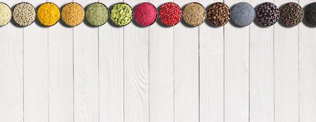 Zestaw przypraw w ziołach na białym stole. wielokolorowe przyprawy z pustym tłem