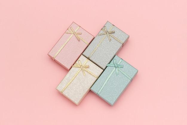 Zestaw pudełek pastelowych kolorów na różowym tle, widok z góry