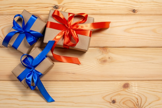 Zestaw pudełek zawiniętych w papier rzemieślniczy i zawiązany czerwoną satynową i niebieską wstążką