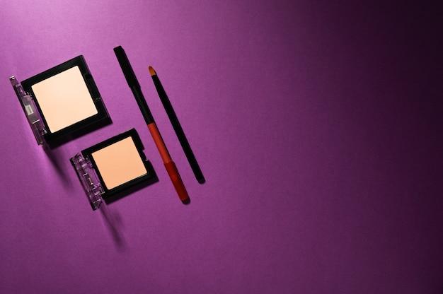 Zestaw pudru do konturowania do korekcji skóry twarzy, eyeliner i profesjonalny pędzel maquillage na ciemnofioletowym odcieniu