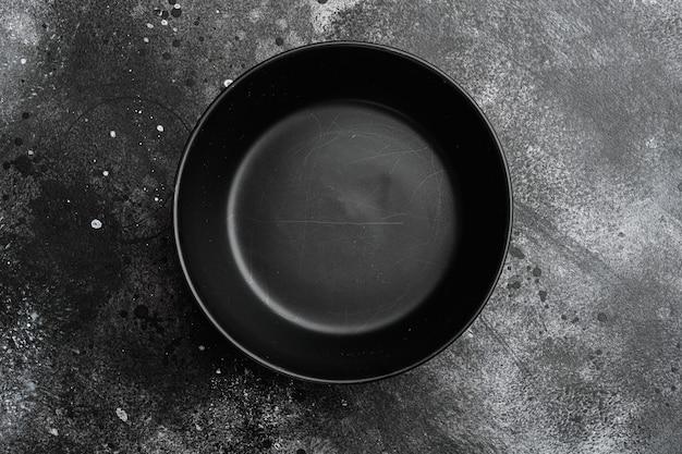 Zestaw pustych czarnych misek, z miejscem na kopię na tekst lub jedzenie, z miejscem na kopię na tekst lub jedzenie, widok z góry płasko leżący, na tle czarnego ciemnego kamiennego stołu