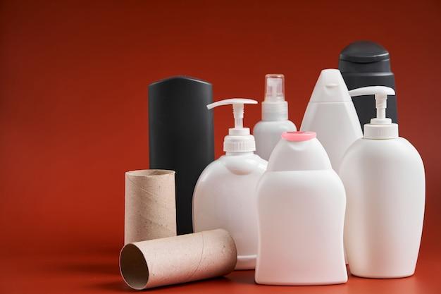 Zestaw pustych, czystych plastikowych pojemników o różnych kształtach z domowych środków czystości, przyborów prysznicowych i tekturowej tuby po papierze toaletowym.