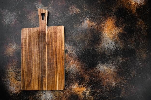 Zestaw pustych desek do krojenia, płaski widok z góry, z kopią miejsca na tekst lub jedzenie, na starym ciemnym tle rustykalnym stołu