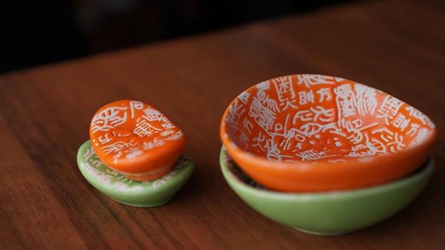 Zestaw pustych zielonych i pomarańczowych naczyń ceramicznych i stojaków na paluszki sushi na drewnianym tle