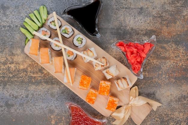 Zestaw pysznego sushi z pałeczkami i imbirem na marmurowej powierzchni