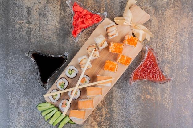 Zestaw pysznego sushi z pałeczkami i imbirem na marmurowej przestrzeni