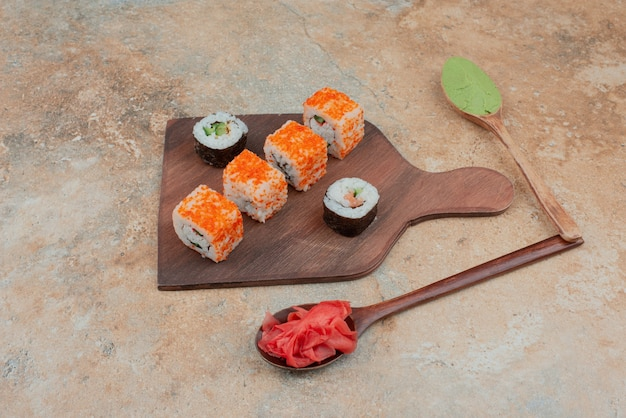 Zestaw pysznej rolki sushi z łyżeczką i sosem sojowym na marmurze