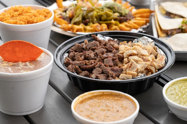 Zestaw pysznych dań kuchni meksykańskiej z wołowiną i kurczakiem, salsami, dipem z fasoli z frytkami i ryżem