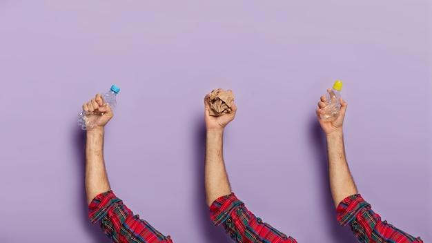 Zestaw rąk człowieka z pokruszonymi plastikowymi butelkami nadającymi się do recyklingu