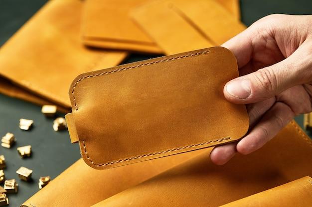 Zestaw ręcznie robionych galanterii skórzanej w męskich rękach, breloczki, portfel, torebka, notatnik, podręcznik. ręcznie robione wyroby skórzane, zbliżenie.