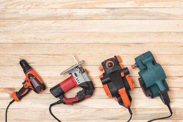 Zestaw ręcznych elektronarzędzi stolarskich do obróbki drewna leży na jasnym tle drewnianych. bezpośrednio powyżej