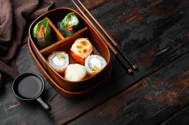 Zestaw rolek bento sushi, na starym ciemnym drewnianym stole