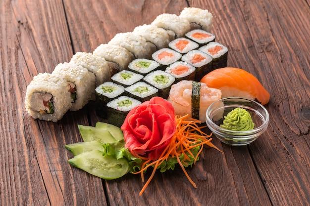 Zestaw rolek i sushi na drewnianym stole.